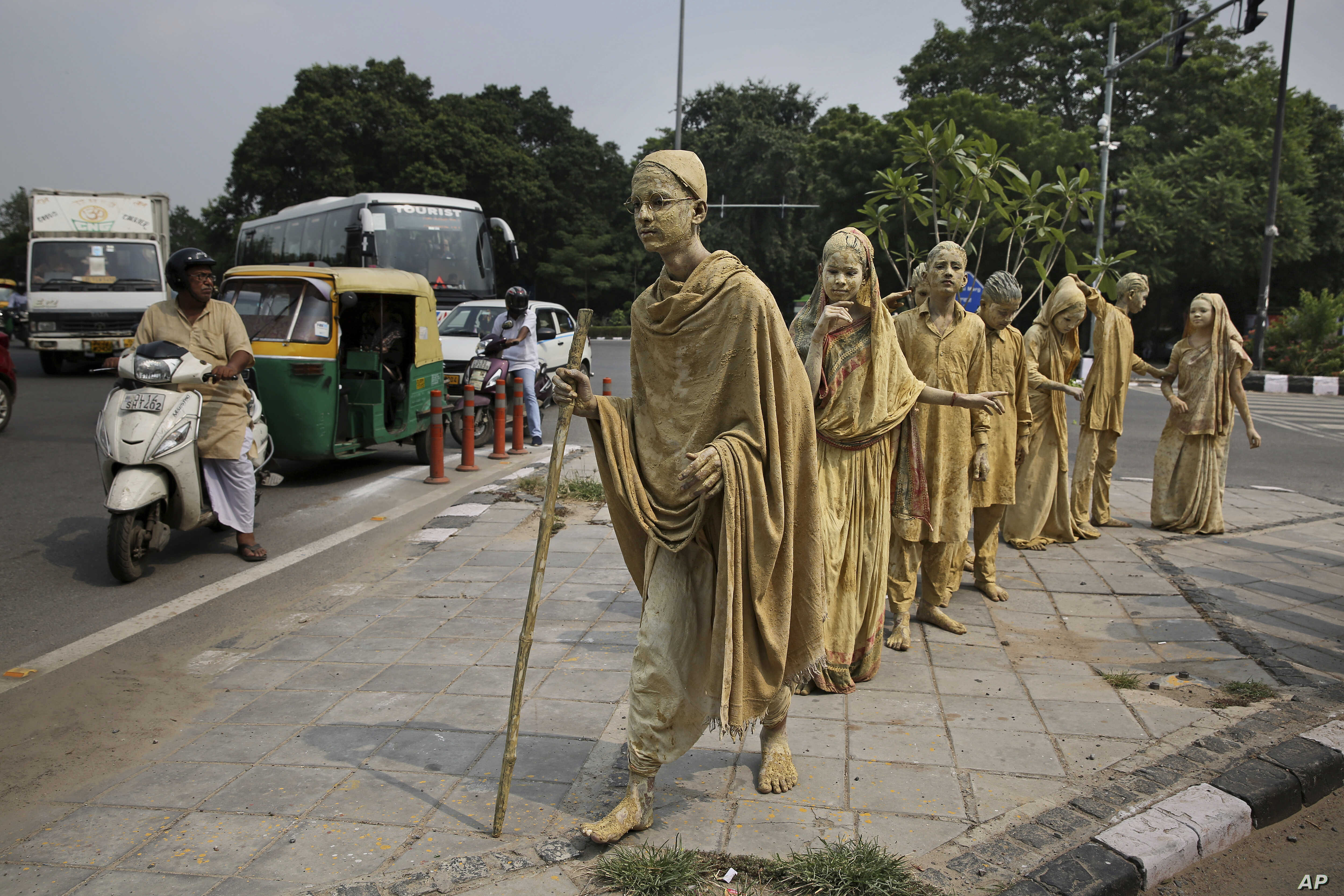 School children dressed up as statues, depicting Indian freedom leader Mahatma Gandhi's Dandi March, stand at a traffic intersection on the eve of Gandhi's 150th birth anniversary in New Delhi.