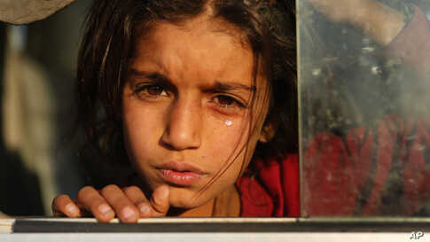 A Syrian girl, newly displaced by the Turkish military operation in northeastern Syria, cries as she sits in a bus upon her arrival at the Bardarash camp, north of Mosul, Iraq.