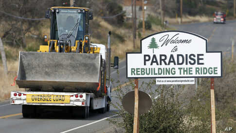 """Vehicles pass a sign welcoming people to Paradise, Calif., Tuesday Nov. 5, 2019. The sign also displays the slogan, """"Rebuilding…"""