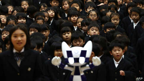 Schoolchildren pose for a picture with Tokyo 2020 Olympic Games' robot-type mascot Miraitowa during a ceremony at Hoyonomori elementary school in Tokyo, Japan.