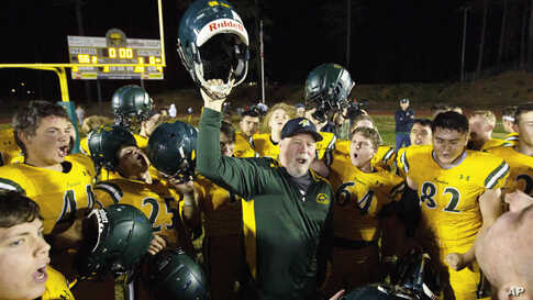 Paradise High School head football coach Rick Prinz, center, celebrates with his team after defeating Live Oak High School, 56-0, in their Northern California Division III playoff game in Paradise, Calif., Nov. 15, 2019.