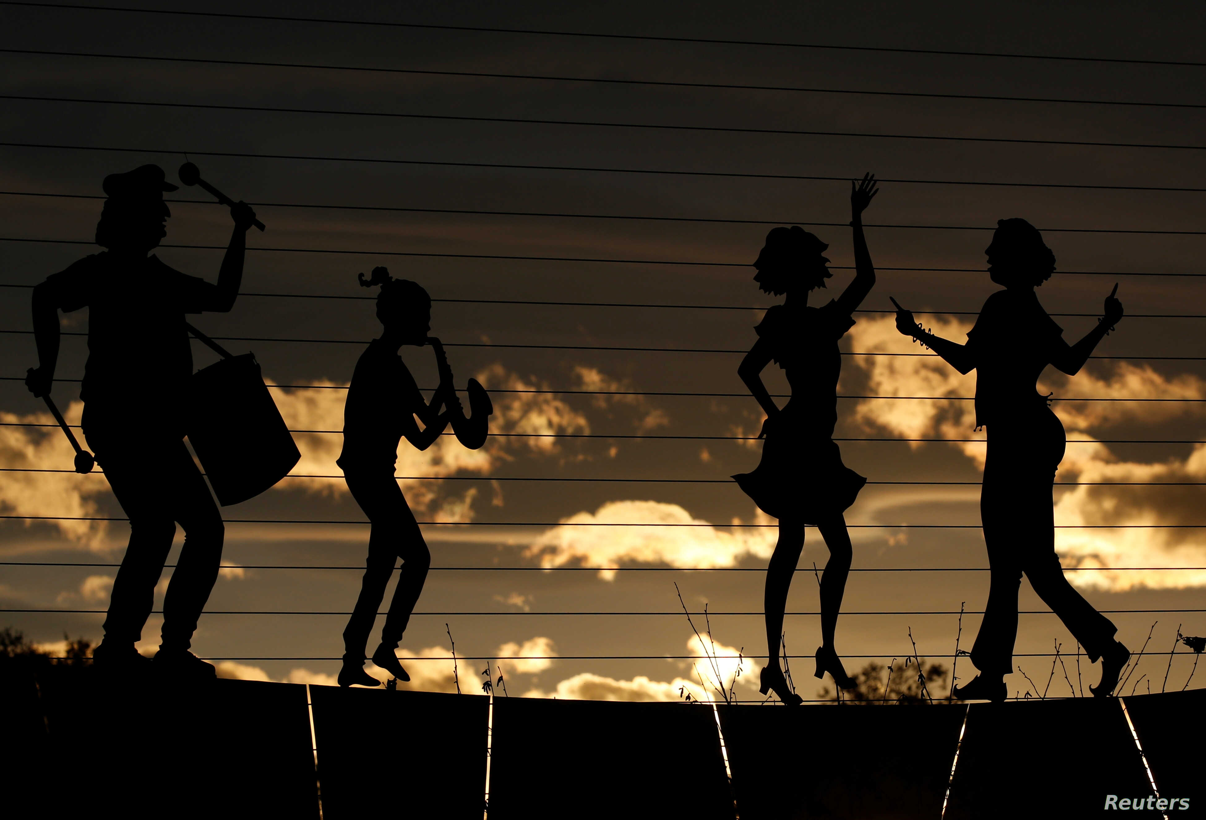 The sun sets behind cut-outs of musicians and dancers in Pau, France.