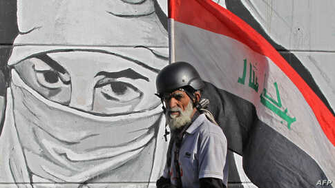 An Iraqi protester carrying his national flag walks past graffiti during ongoing anti-government protests, at Tahrir square in the capital Baghdad, Dec. 20, 2019.