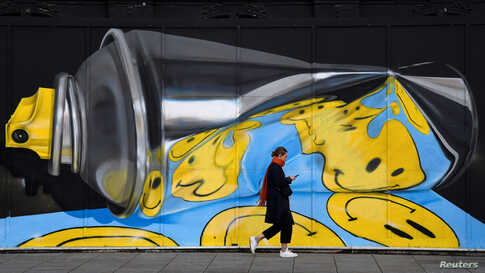 A woman views her phone as she walks past street art on a wall in London, Britain, Dec. 18, 2019.