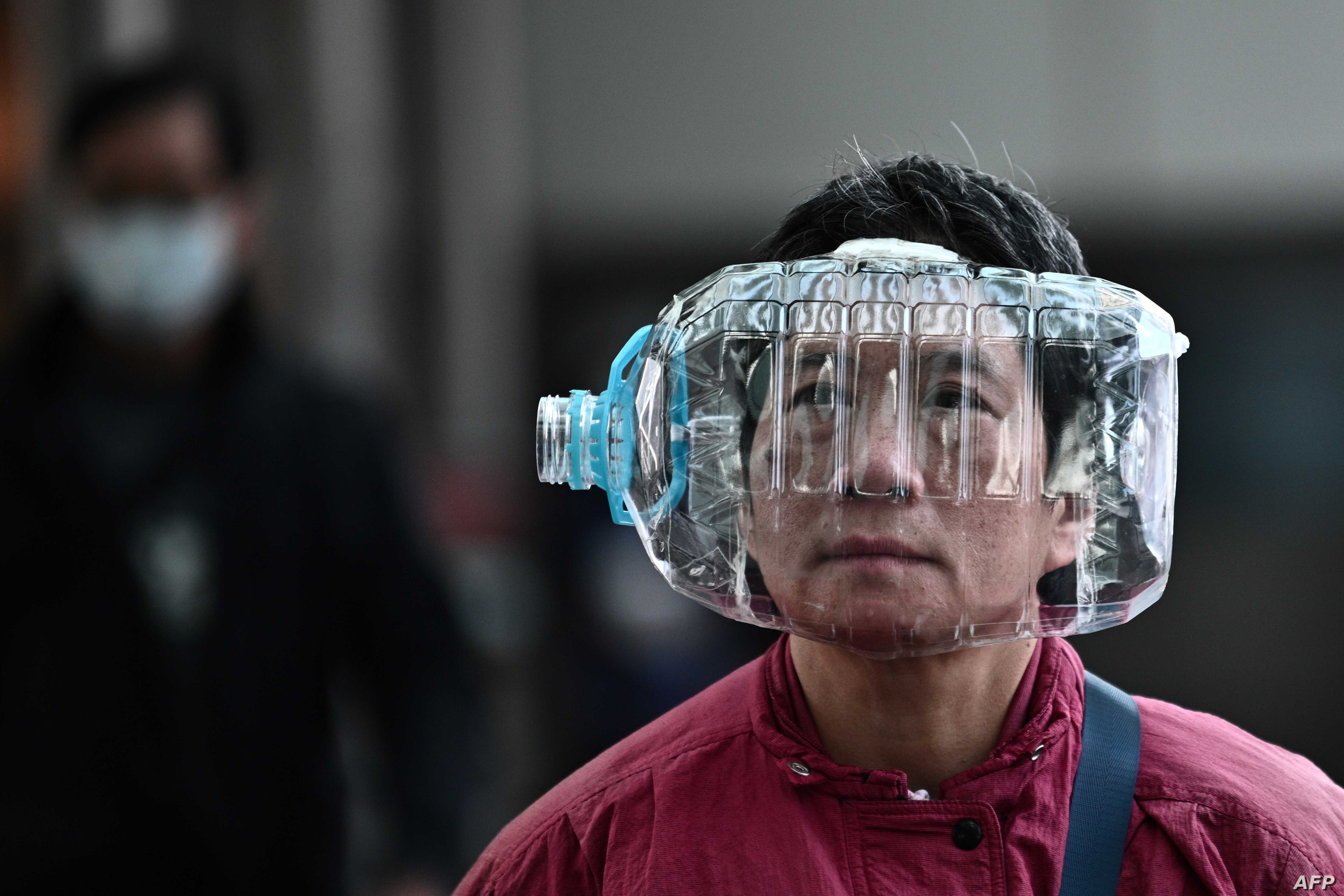 A woman wears a plastic water bottle with a cutout to cover her face, as she walks on a footbridge in Hong Kong on January 31,…