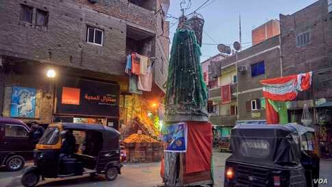 """Residents of """"Garbage City,"""" a largely Coptic neighborhood of eastern Cairo, put up a Christmas tree made of materials including recycled plastic."""