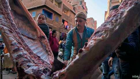 Cairo butchers do brisk business the day before Christmas. After Christmas Eve Mass, Coptic Orthodox Christians break a long meatless fast.