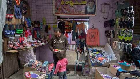 A father buys shoes for his daughter ahead of Christmas. (Hamada Elrasam/VOA)