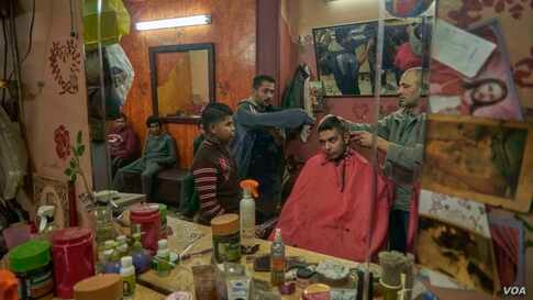 Aiming to look their best on a special day, men get haircuts as they prepare to celebrate the feast with their families and friends.