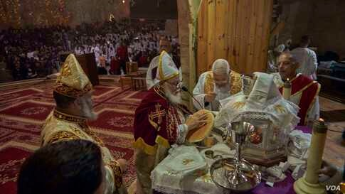 Coptic priests sing in praise as they consecrate bread during Christmas Mass. (Hamada Elrasam/VOA)