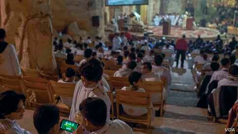 Some 21st century pastimes clash with ancient traditions as young worshipers play a video game during Christmas Mass. (Hamada Elrasam/VOA)