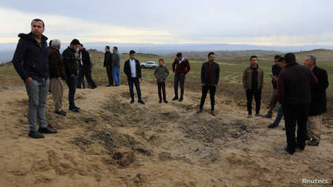 Residents look at a crater caused by a missile launched by Iran on U.S.-led coalition forces on the outskirts of Duhok, Iraq,…