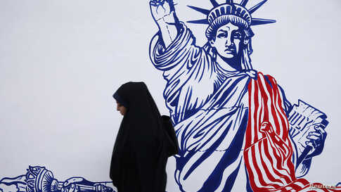 A woman walks in front of new murals of the former US embassy in Tehran, Iran November 2, 2019. Nazanin Tabatabaee/WANA (West…