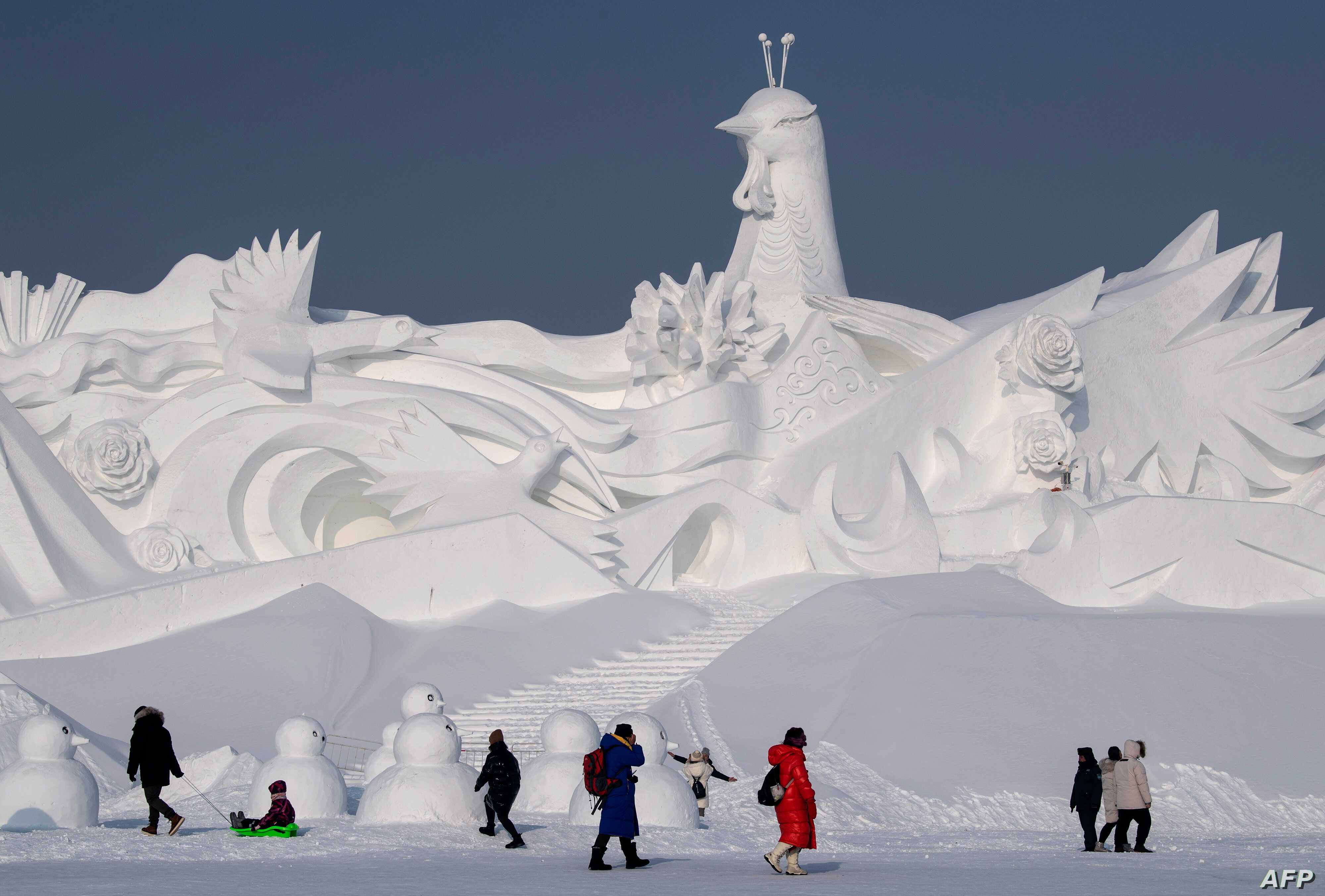 Tourists walk in front of an ice sculpture ahead of the opening of the Harbin International Snow and Sculpture Festival in Harbin, in China's northeast Heilongjiang province, Jan. 4, 2020.