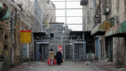 Two Palestinian women approach a checkpoint to cross into the Israeli-controlled Shuhada Street in the divided town of Hebron, in the Israeli occupied West Bank.