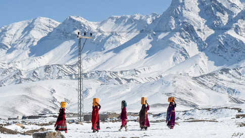 Local residents carry water pots above their heads as they walk back to their homes after heavy snowfall in Khanozai area some 75 kms in northeast of the provincial capital Quetta, Pakistan.