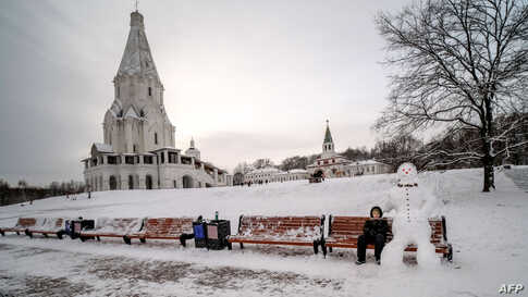 A boy sits next to a snowman in Kolomenskoye park in Moscow, Russia.