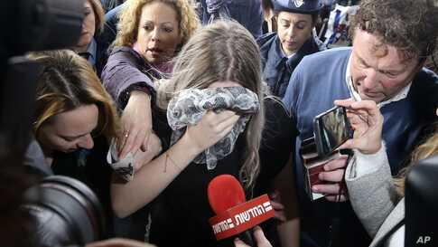 A 19 year-old British woman, center, who was found guilty of making up claims that she was raped by up to 12 Israelis, arrives at Famagusta District Court for sentencing in Paralimni, Cyprus.