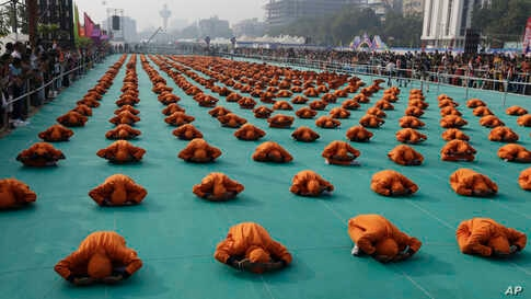 Indian school children perform yoga during the inauguration of an international kite festival in Ahmadabad, India.