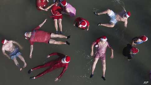 Members of a group of trained Santa Clauses from Europe and the USA float in the Dead Sea near the West Bank city of Jericho.