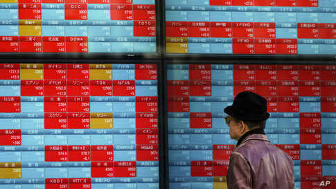 A man looks at an electronic stock board showing Japan's Nikkei 225 index at a securities firm in Tokyo.