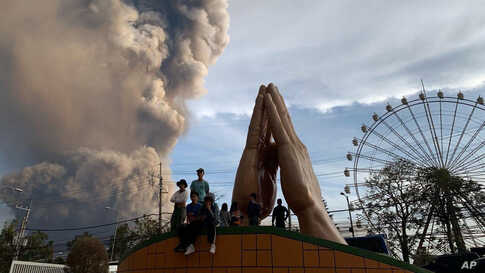 People watch as the Taal volcano spews ash and smoke during an eruption in Tagaytay, Cavite province south of Manila,…
