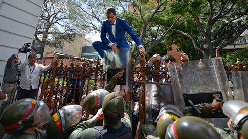 Venezuela's National Assembly President and opposition leader Juan Guaido tries to climb the fence to enter the compound of the Assembly in Caracas, after he and other opposition lawmakers were blocked by police, Jan. 5, 2020.