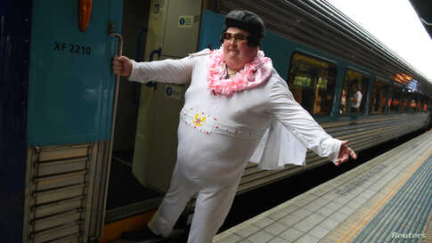 Sean Wright poses for a photo before boarding the Elvis Express, bound for Parkes for the Elvis festival, at Central Station in Sydney, Australia.