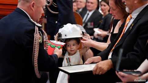 Charlotte O'Dwyer, the daughter of Rural Fire Service volunteer Andrew O'Dwyer, receives her father's helmet and a service medal by RFS Commissioner Shane Fitzsimmons during his funeral in Horsley Park, Sydney, Australia.
