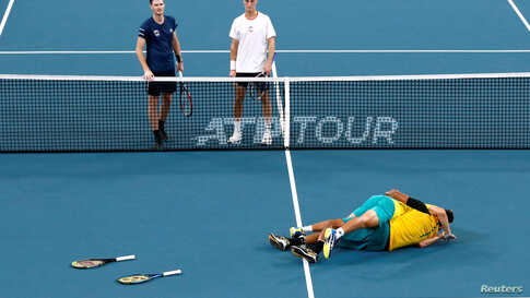Australia's Alex de Minaur and Nick Kyrgios celebrate winning their Quarter Final doubles match against Britain's Jamie Murray and Joe Salisbury as they look on dejected at the ATP Cup in Sydney, Australia.