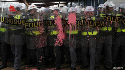 Riot police officers are seen with their shields stained with paint thrown by demonstrators, who are prevented from jumping over turnstiles, after a protest against fare hikes for city buses in Sao Paulo, Brazil, Jan. 7, 2020.