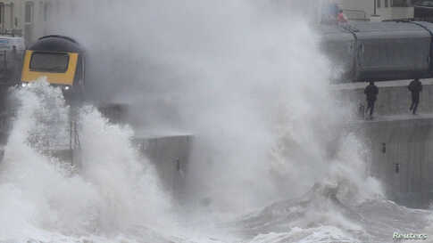 Large waves hit the sea wall with Storm Brendan bringing high winds and heavy rain, as a train passes through Dawlish, southwest Britain.