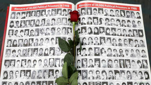 A rose rests on a page featuring photographs of people who have died in Iran as Iranian Americans from across California converge in Los Angeles, Jan. 11, 2020. to participate in the California Convention for a Free Iran.