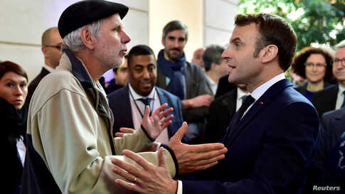 French mathematics teacher Pierre Coste speaks with President Emmanuel Macron about the government's pensions overhaul at the Beaumont Palace in Pau.