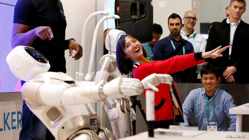 Tanli Yang, a journalist with China Global Television Network, performs yoga poses with Walker, an intelligent humanoid service robot, at the UB Tech booth during the 2020 CES in Las Vegas, Nevada, Jan. 8, 2020.