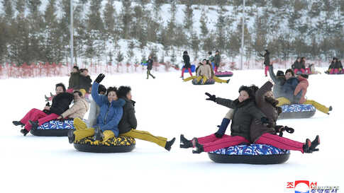 People play in the snow at the Yangdok Hot Spring Resort, North Korea, in this undated photo released by North Korea's Korean Central News Agency (KCNA).