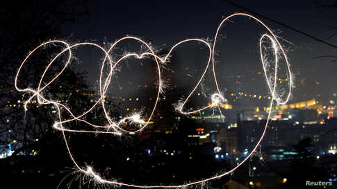 A girl with sparkle writes 2020 during the New Year's celebrations in North Macedonia.