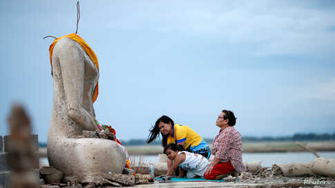 A family prays near the ruins of a headless Buddha statue, which has resurfaced in a dried-up dam due to drought, in Lopburi, Thailand, Aug. 1, 2019.