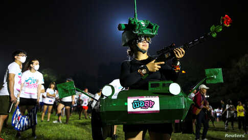 """A runner dressed in a tank costume takes part in the """"Run Against Dictatorship"""" event at a public park in Bangkok, Thailand."""
