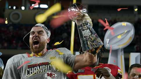 Kansas City Chiefs' Travis Kelce hoists the trophy after defeating the San Francisco 49ers in the NFL Super Bowl 54.