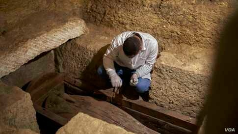 Egyptian archaeologist Ashraf Saad provides first aid to one of 5 wooden coffins found at the Al-Ghoreifa area in Tuna El-Gabal archaeological site in Minya. (Hamada Elrasam/VOA)