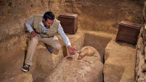 Archeological inspector Wahballah explains the inscriptions of titles, names engraved on sarcophagi of Dejd Dejhuty Iuf Ankh, who was the royal treasurer and bearer of seals of Lower Egypt. (Hamada Elrasam/VOA)