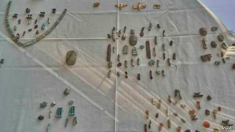 """The Egyptian archeological mission also uncovered more than 700 amulets of various entities, including amulets of the gods, heart scarabs, and pure gold amulets such as the """"Ba"""" and an amulet in the shape of a winged cobra. (Hamada Elrasam/VOA)"""