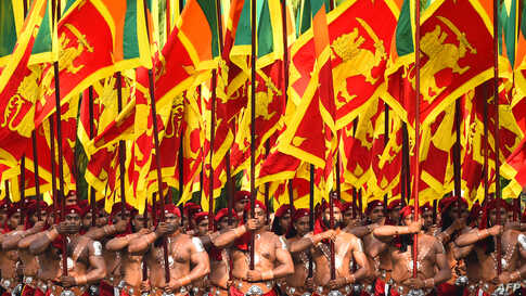 Sri Lankan military personnel march in traditional dress holding national flags during the country's 72nd Independence Day celebrations in Colombo.