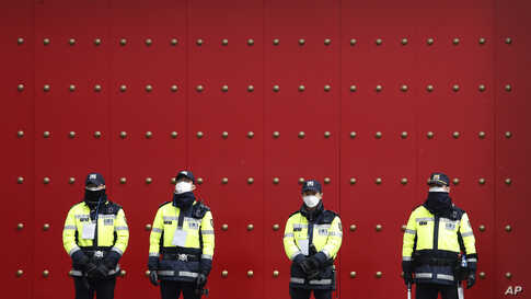 Police officers stand guard as protesters stage a rally calling for a ban on Chinese people entering South Korea in front of the Chinese embassy in Seoul, South Korea.