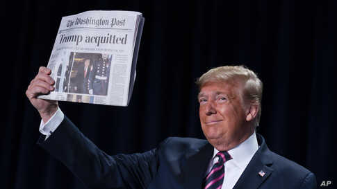 """President Donald Trump holds up a newspaper with the headline that reads """"Trump acquitted"""" during the 68th annual National Prayer Breakfast, at the Washington Hilton in Washington, D.C."""