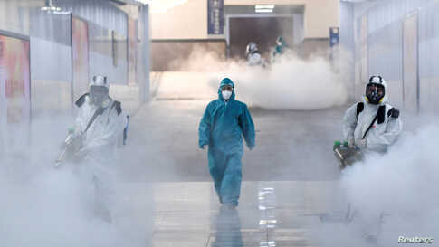 Volunteers in protective suits disinfect a railway station as the country is hit by an outbreak of the new coronavirus, in Changsha, Hunan province, China.