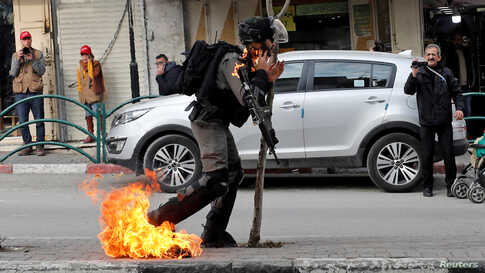 An Israeli border policeman is on fire as he is hit with a molotov cocktail thrown by Palestinian demonstrators during a protest against the U.S. President Donald Trump's Middle East peace plan, in Hebron in the Israeli-occupied West Bank, Feb. 3, 2020.