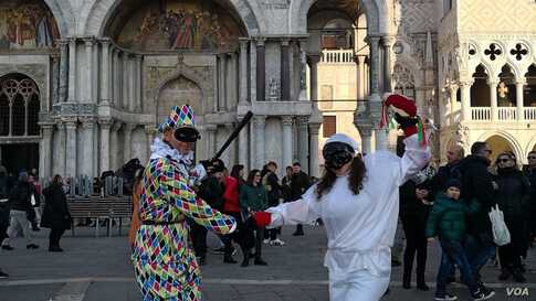 A couple in costume strike a pose at Saint Mark's Square as the carnival was set to kick off, in Venice, Italy, Feb. 8, 2020.