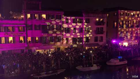A light show at the Venice Carnival is played on the buildings along the canals, in Venice, Italy, Feb. 8, 2020.